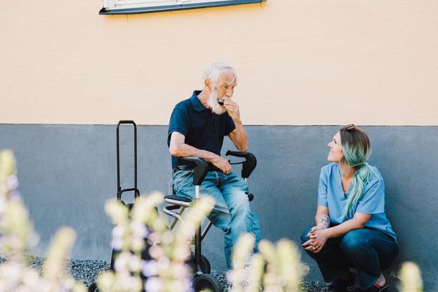 Leende sköterska sitter bredvid äldre man i trädgård på äldreboende