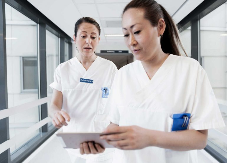 Doctor and nurse with mobile EHR electronic health recond on ipad
